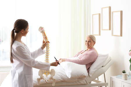 Female orthopedist explaining structure of spine to patient in clinic