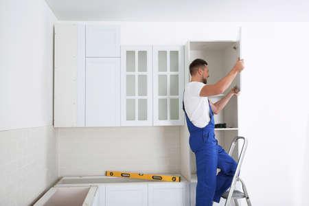 Worker installing door of cabinet in kitchen 写真素材