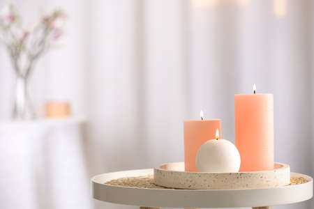 Burning candles on table indoors. Space for text