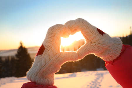 Woman making heart with hands outdoors at sunset, closeup. Winter vacation Foto de archivo