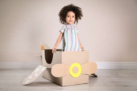 Cute African American child playing with cardboard plane near beige wall