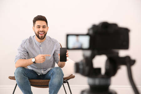 Young blogger with smartphone recording video on camera indoors