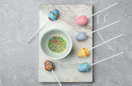 Egg shaped cake pops for Easter celebration on grey marble table, flat lay Stock Photo