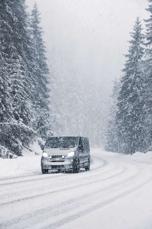 Snowy country road with modern car on winter day