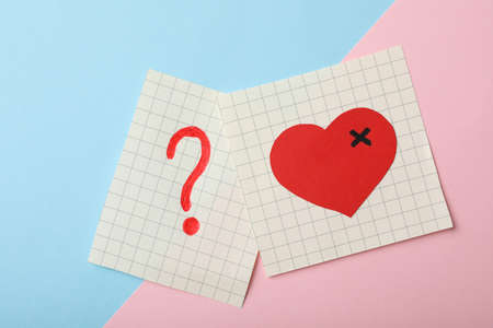 Paper notes with drawings of heart and question mark  on color background, flat lay. Relationship problems concept
