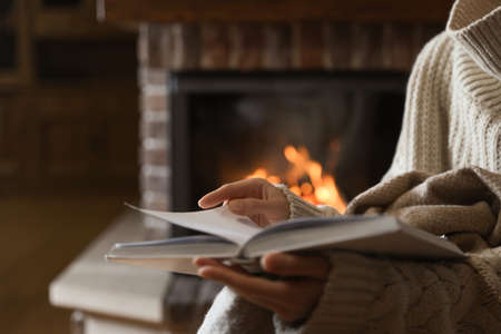 Woman reading book near burning fireplace at home, closeup Imagens