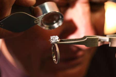 Professional jeweler evaluating beautiful ring, closeup view