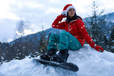 Young snowboarder wearing Santa hat on snowy hill. Winter vacation Stock Photo