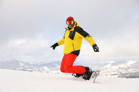 Male snowboarder on snowy hill. Winter vacation