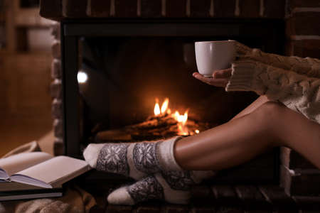 Woman with cup of hot cocoa near fireplace indoors, closeup