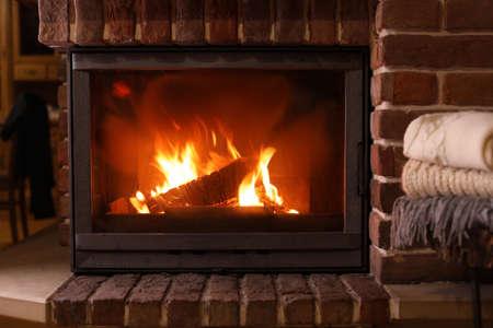 Pile de tricots près de la cheminée avec du bois brûlant à l'intérieur. Vacances d'hiver
