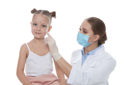Doctor examining little girl with chickenpox on white background. Varicella zoster virus