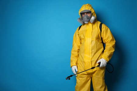 Man wearing protective suit with insecticide sprayer on blue background, space for text. Pest control