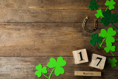 Flat lay composition with clover leaves and block calendar on wooden background, space for text. St. Patrick's day Stockfoto