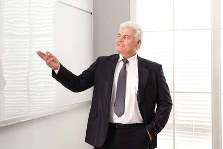 Senior business trainer near whiteboard in office Standard-Bild