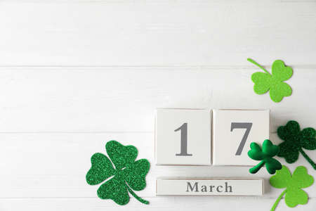 Flat lay composition with block calendar on white wooden background, space for text. St. Patrick's Day celebration