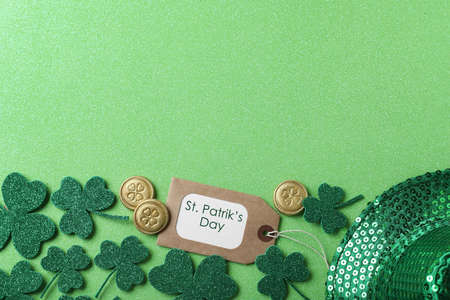 Clover leaves and tag with phrase St. Patrick's Day on light green background, flat lay. Space for text Stock Photo