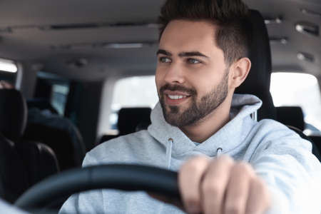 Handsome young man driving his modern car