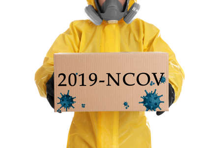 Man wearing chemical protective suit with cardboard box on white background, closeup. Coronavirus outbreak