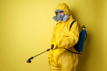 Man wearing protective suit with insecticide sprayer on yellow background. Pest control Archivio Fotografico