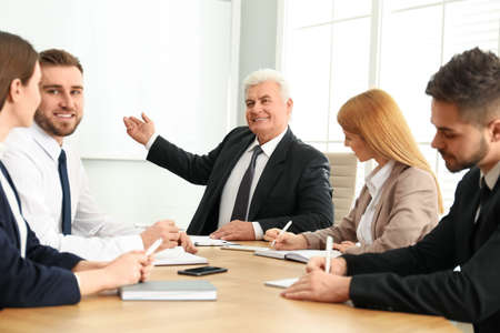 Senior business trainer working with people in office