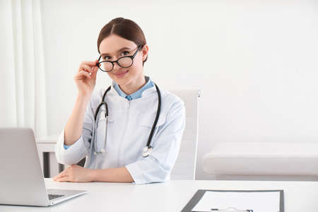 Portrait of young female doctor in white coat at workplace Stock Photo