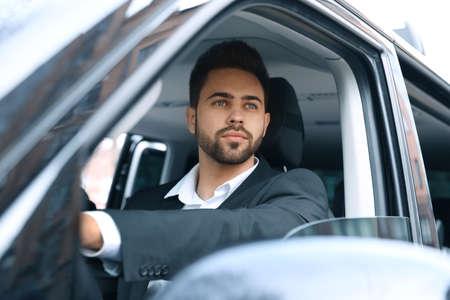 Beau jeune homme au volant de sa voiture moderne