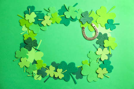 Frame made of clover leaves and horseshoe on green background, flat lay with space for text. St. Patrick's day