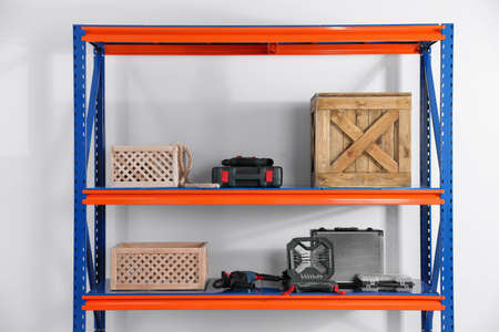 Metal shelving unit with wooden crates and different instruments on light background