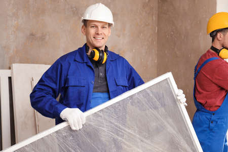 Workers in uniform installing plastic window indoors
