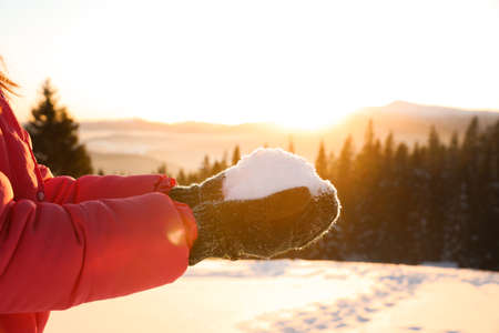 Woman holding pile of snow outdoors, closeup. Winter vacation