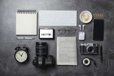 Flat lay composition with equipment for journalist on grey table