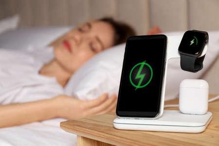 Smartphone, watch, earphones charging on wireless pad and sleeping woman in room Stockfoto