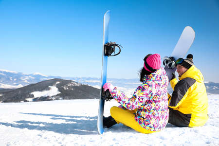 Couple with snowboards on hill, space for text. Winter vacation