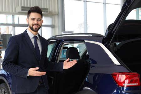 Young salesman near new car in dealership Stockfoto
