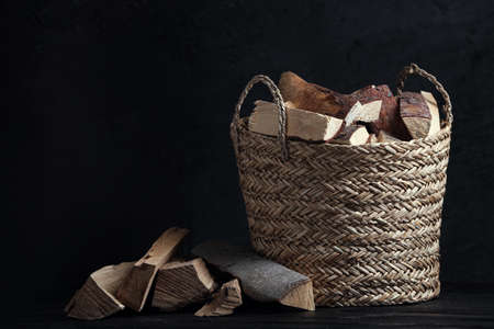 Wicker basket with cut firewood on table against dark background