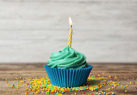 Delicious birthday cupcake with cream and burning candle on wooden table