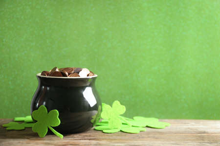 Pot of gold coins and clover leaves on wooden table against green background, space for text. St. Patrick's Day celebration