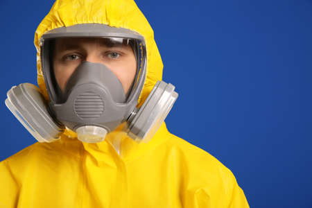 Man wearing chemical protective suit on blue background, closeup. Virus research