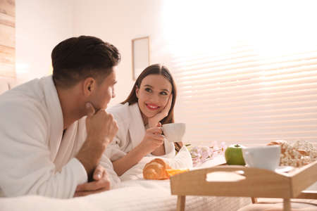 Happy couple in bathrobes having breakfast on bed at home