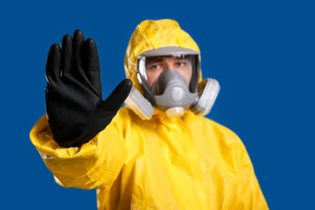 Man in chemical protective suit making stop gesture against blue background, focus on hand. Virus research Фото со стока