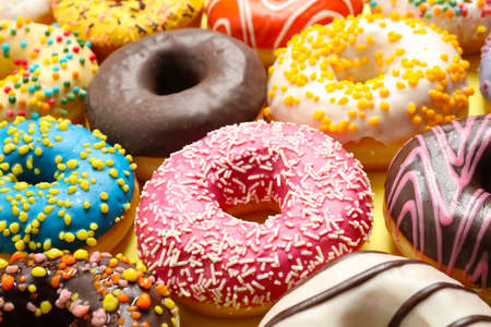 Delicious glazed donuts on yellow background, closeup Stock fotó