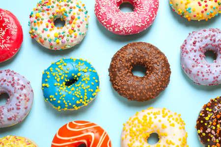 Delicious glazed donuts on light blue background, flat lay Standard-Bild
