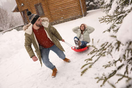 Young man pulling sled with his girlfriend outdoors on snowy day. Winter vacation