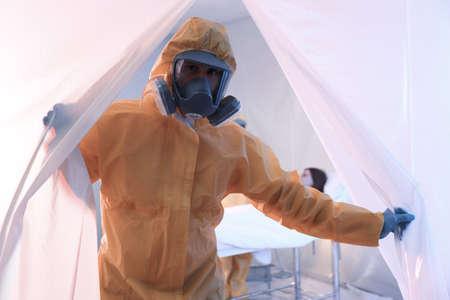 Paramedic standing near entrance to quarantine ward. Virus awareness