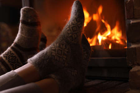 Couple resting near fireplace indoors, closeup. Winter vacation