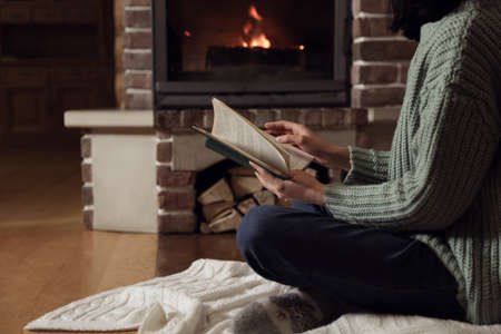 Woman reading book near burning fireplace at home, closeup Imagens