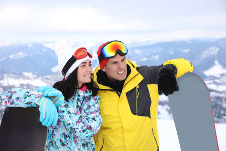 Couple with snowboards at mountain resort. Winter vacation