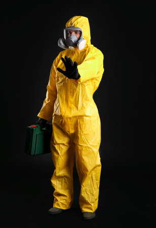 Man in chemical protective suit on black background. Virus research