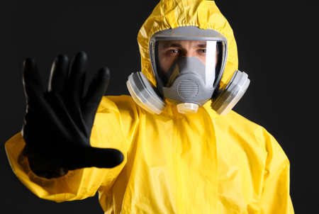 Man in chemical protective suit making stop gesture on black background. Virus research
